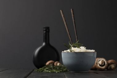 bowl of rice with mushrooms and bottle of soy sauceon black tabletop