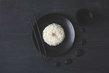 top view of tasty rice on plate with chopsticks on black table
