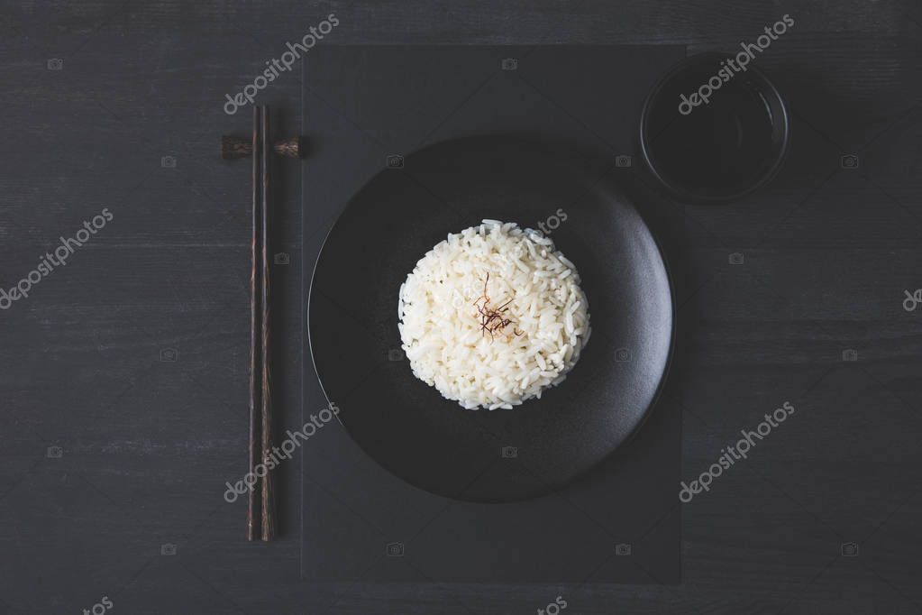 top view of rice with cup of tea and chopsticks on black table