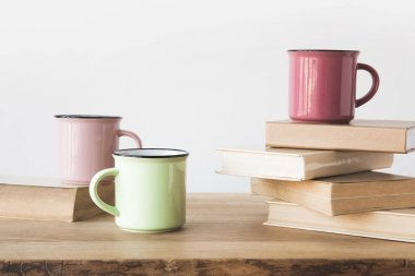 Three colored cups and books on wooden table on white stock vector