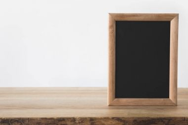 one empty blackboard on wooden table on white