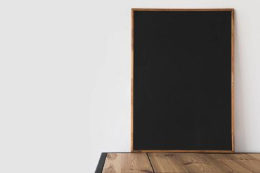 One big empty blackboard on wooden table on white stock vector