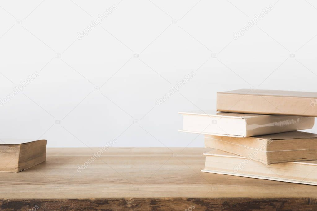 stack of old books on wooden table on white