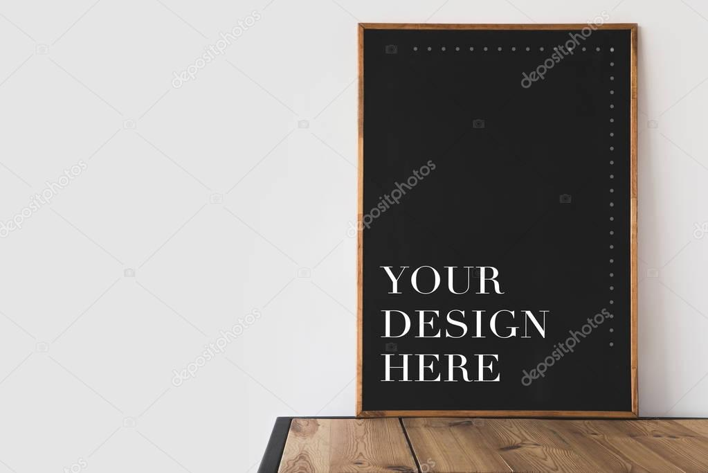 big blackboard with text your design here on wooden table on white