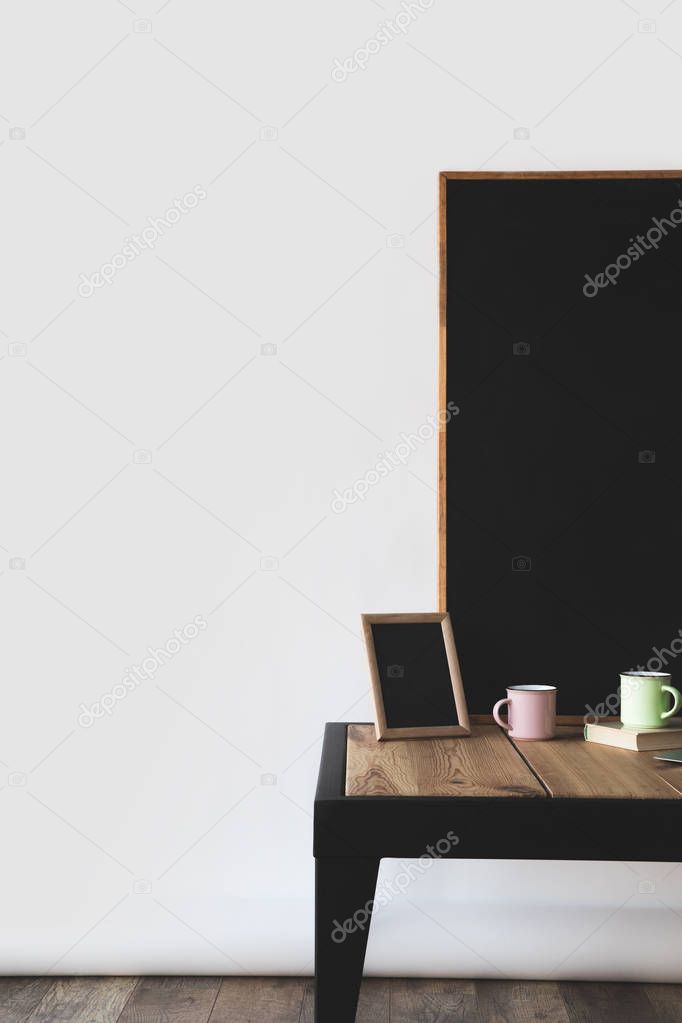 empty blackboards in frames with cups and book on white