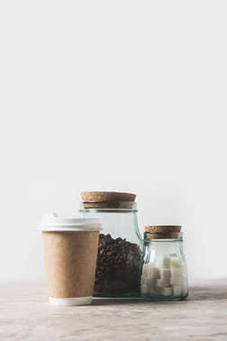 coffee beans, refined sugar and disposable coffee cup on marble table on white