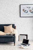 Photo partial view of modern living room interior with cozy couch and picture on white brick wall, mockup concept