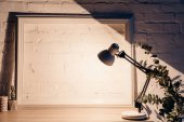 Photo table lamp illuminating white empty brick wall with frame, mockup concept