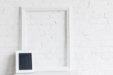 blank frame and small chalkboard in front of white brick wall, mockup concept