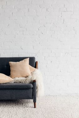 cropped shot of couch with pillows and blanket in living room with white brick wall, mockup concept