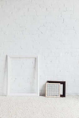 picture frames with leaning on white brick wall, mockup concept