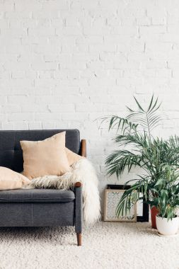 Comfy couch with flowerpots in white living room interior with brick wall, mockup concept stock vector