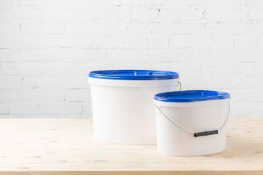 two plastic buckets with paints on wooden table