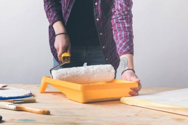 cropped image of woman putting paint roll brush in white paint at wooden table
