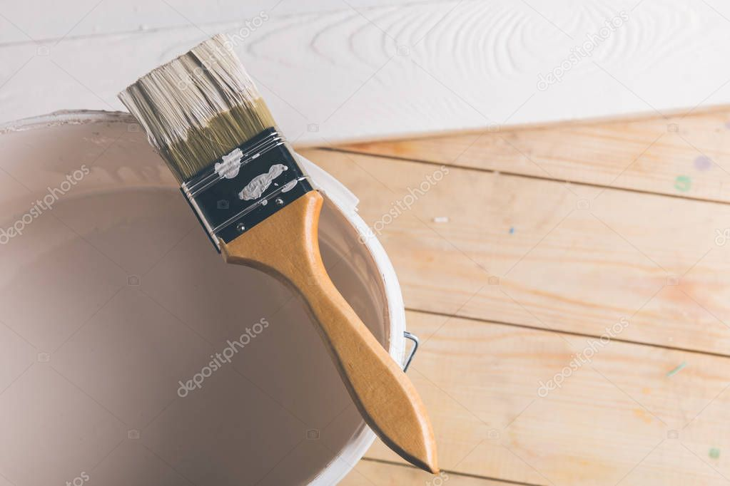 brush on plastic bucket with white paint