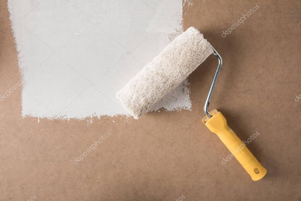 paint roll brush in white paint on plywood surface