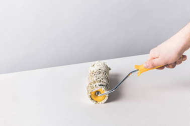 cropped image of woman painting surface with paint roll brush