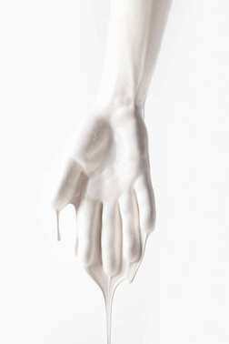 cropped image of female arm in white dripping paint isolated on white
