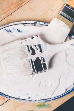 top view of brushes in white paint on cover from bucket