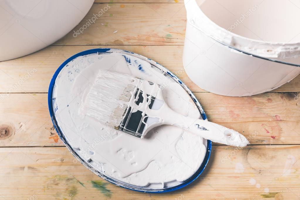 brush in white paint on cover from bucket