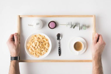 cropped shot of man holding tray with breakfast on white surface