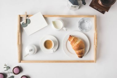 flat lay with cup coffee and croissant for breakfast on tray on white tabletop