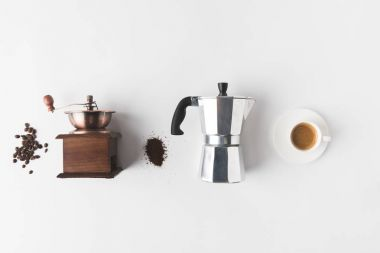 top view of arranged coffee making supplies, ingredients and cup of coffee on white tabletop