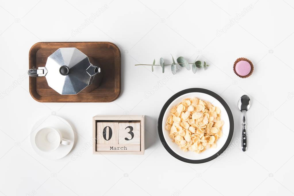 flat lay with corn flakes in bowl for breakfast, coffee maker and cup of coffee on white surface