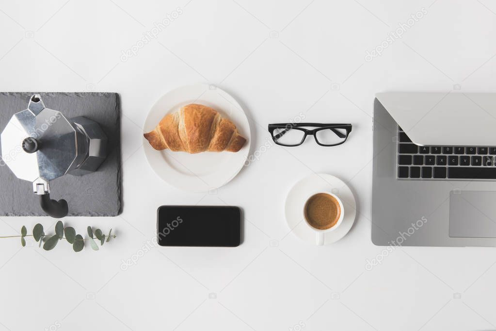 flat lay with digital devices and breakfast on white tabletop