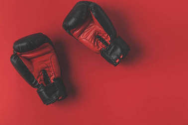 top view of boxing gloves lying on red tabletop