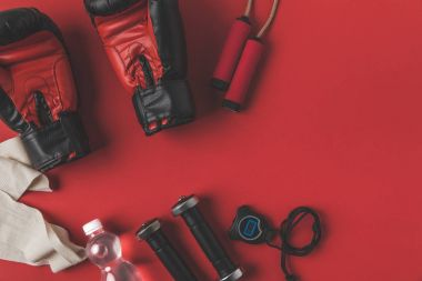 flat lay composition of boxer training equipment on red tabletop