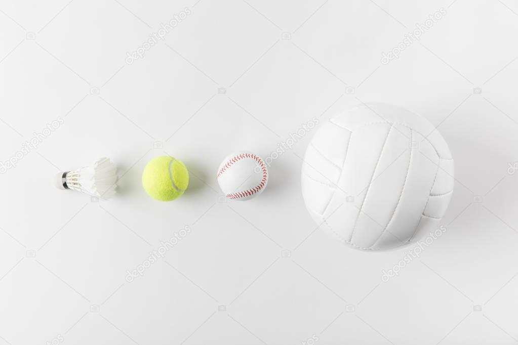 various sports equipment in row on white surface