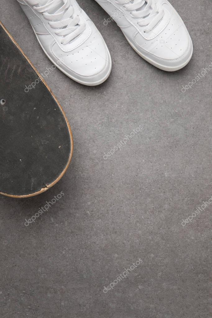 top view of white sneakers and skateboard on gray asphalt surface