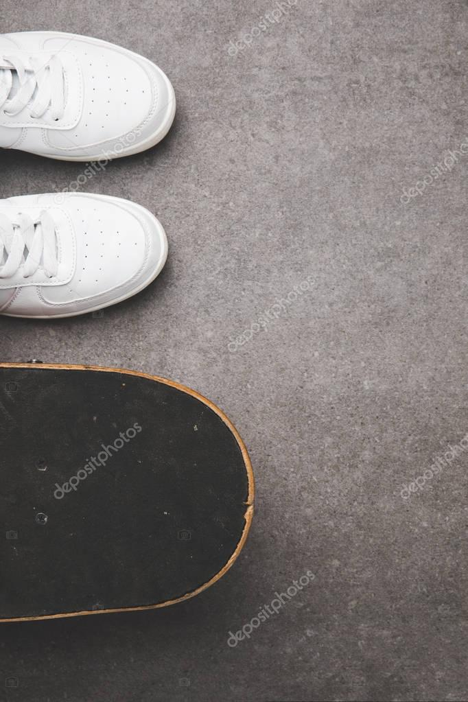 top view of white sneakers and skateboard on concrete surface