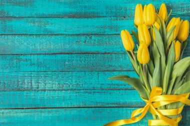 beautiful yellow tulips with ribbon on turquoise wooden surface