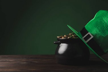 pot of golden coins and green hat on table, st patricks day concept
