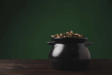 pot of golden coins on wooden table, st patricks day concept