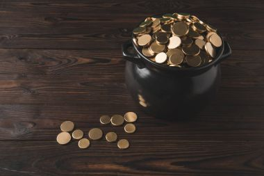 high angle view of pot of golden coins on wooden table, st patricks day concept