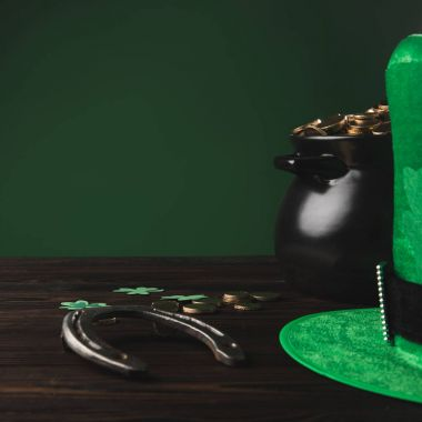 golden coins, horseshoe and green hat on wooden table, st patricks day concept