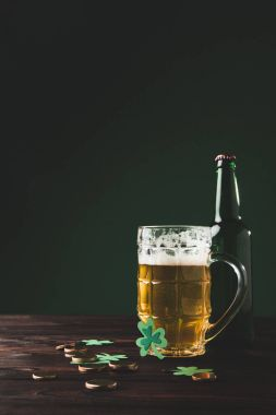 glass of beer with bottle and golden coins on table, st patricks day concept