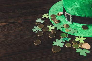 green hat with golden coins and shamrock on wooden table, st patricks day concept