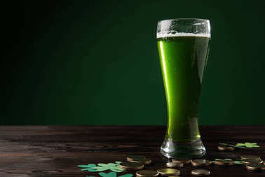 glass of green beer with shamrock and golden coins on table, st patricks day concept