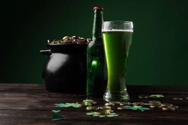 pot with coins and green beer on table, st patricks day concept