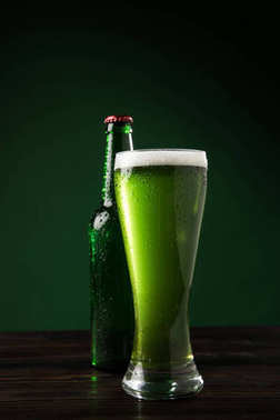 glass bottle and glass of green beer on table, st patricks day concept