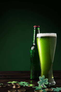 glass bottle and glass of green beer with coins on table, st patricks day concept