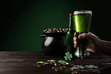 cropped image of man holding glass of green fresh beer, st patricks day concept