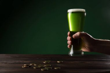 cropped image of man holding glass of green beer above table with coins, st patricks day concept