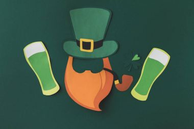 top view of paper decoration of leprechaun and beer for st patricks day isolated on green