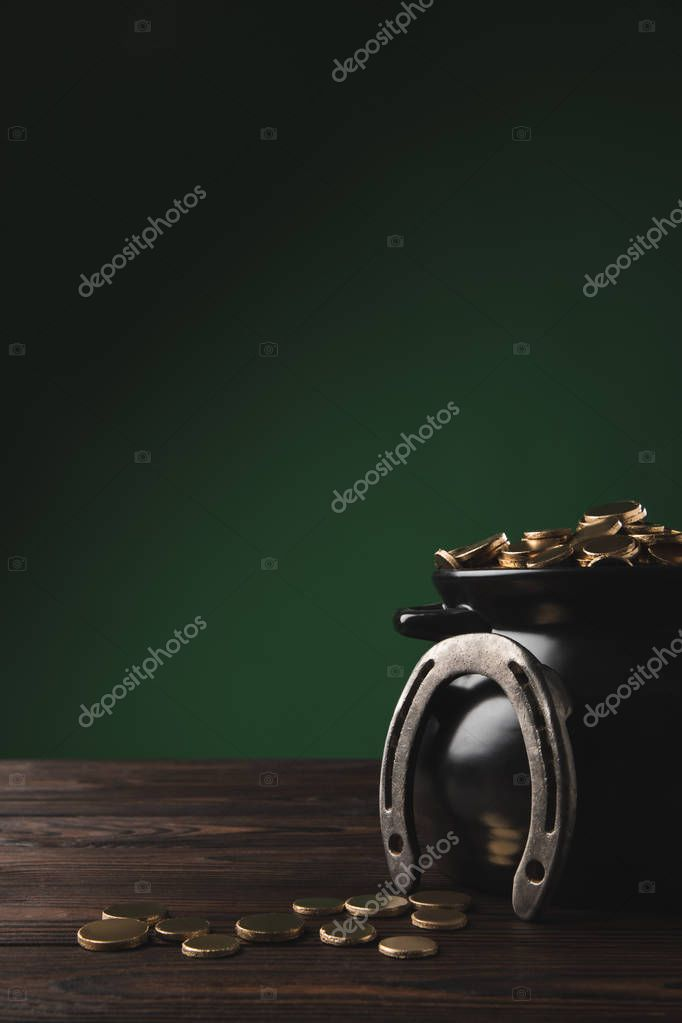 pot with golden coins and horseshoe on table, st patricks day concept