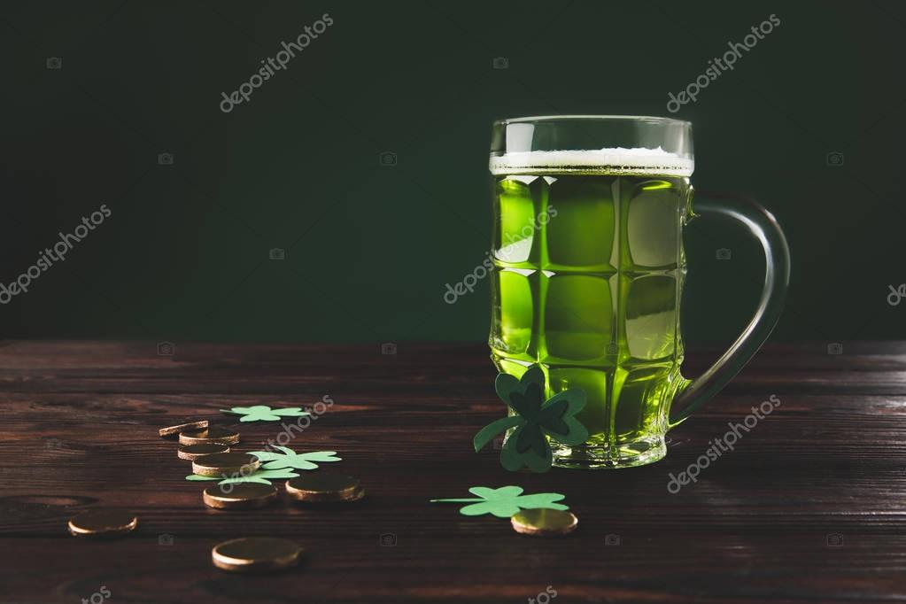 glass of beer with shamrock and golden coins on wooden table, st patricks day concept